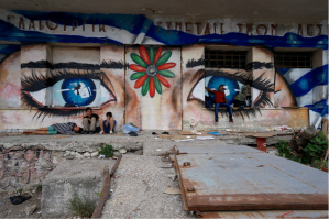 sad eye graffitti wall with people seated in front
